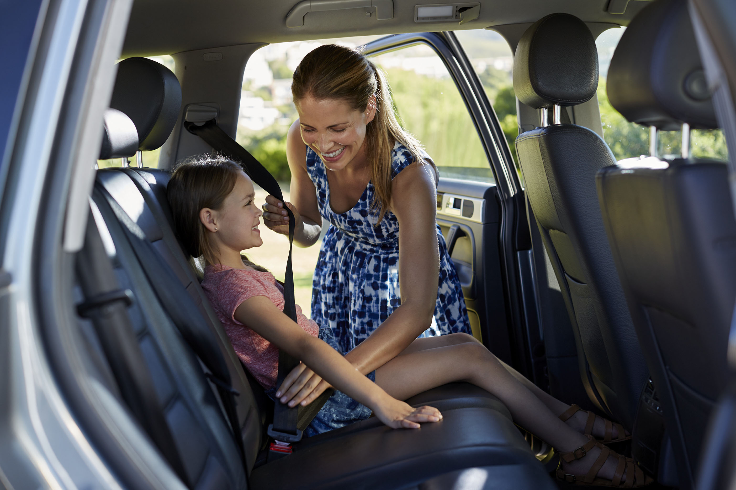 Woman smiling and buckling her daughter's seatbelt