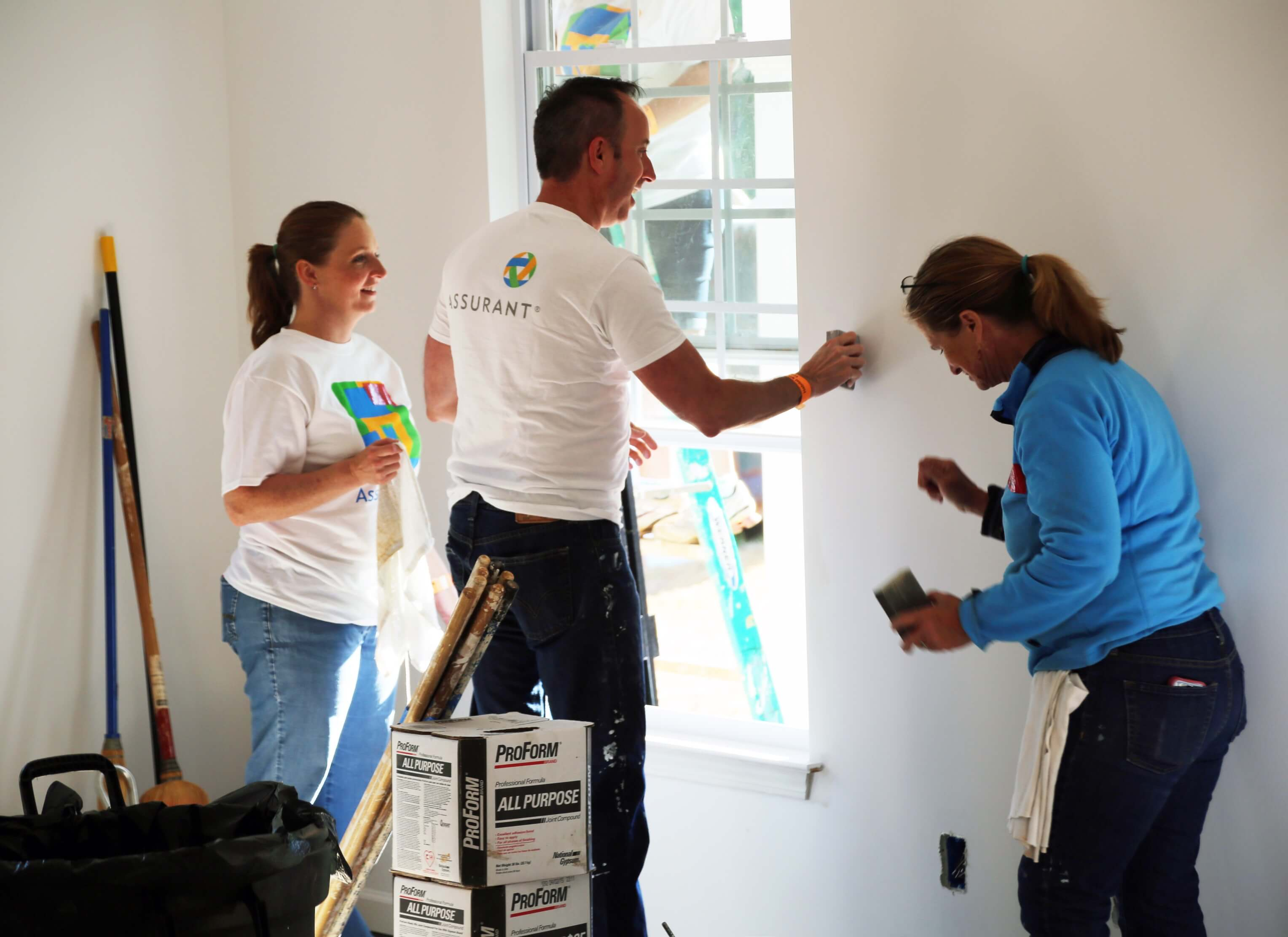 Three Assurant employees working at a Habitat for Humanity build sanding walls