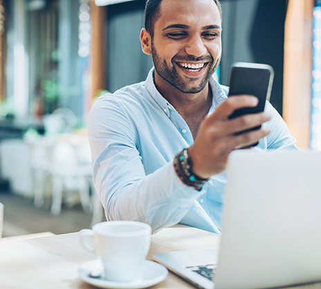 man smiling looking at phone in front of computer