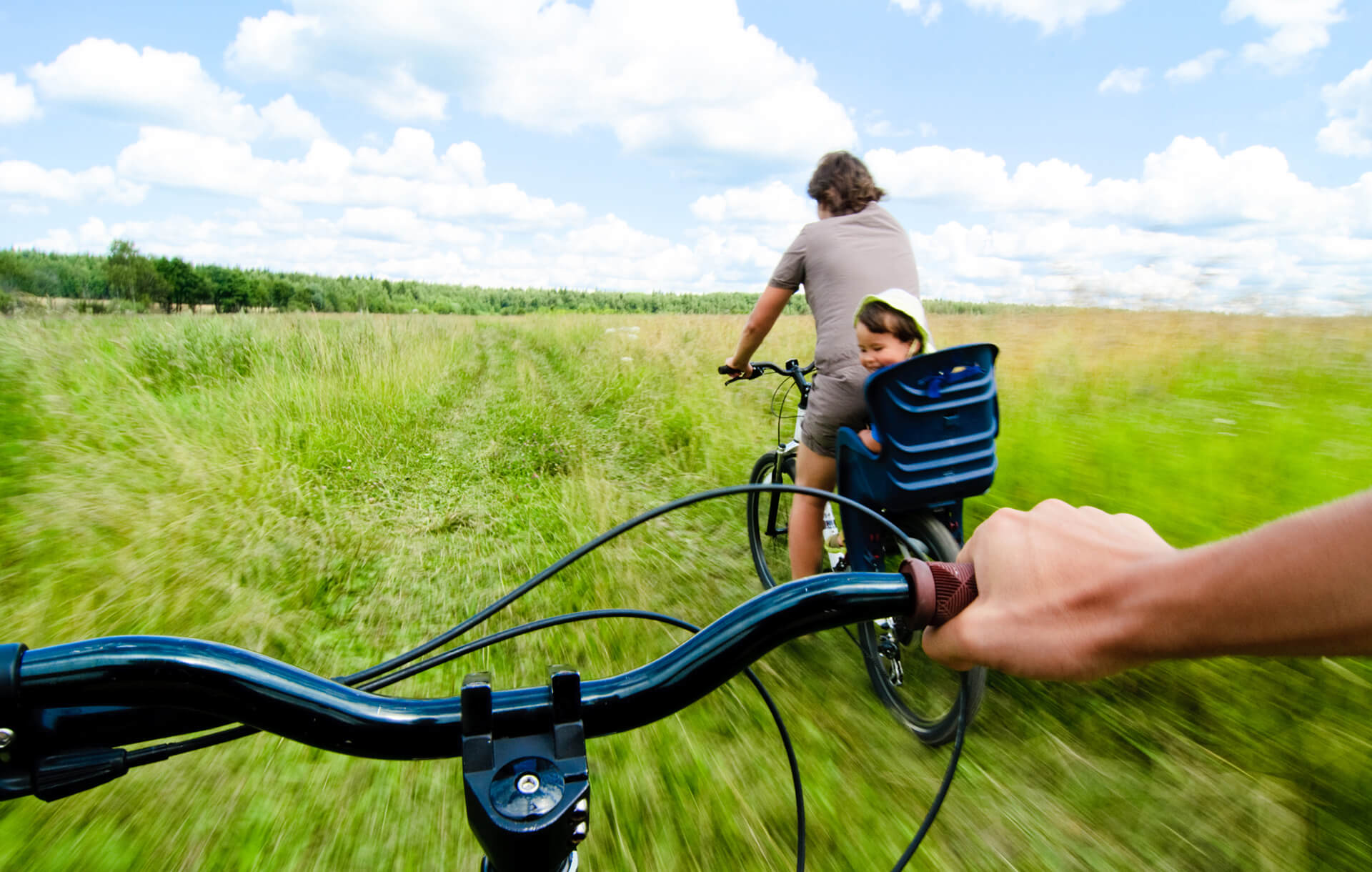 family biking through a green field with baby