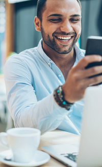 man smiling at phone in front of computer